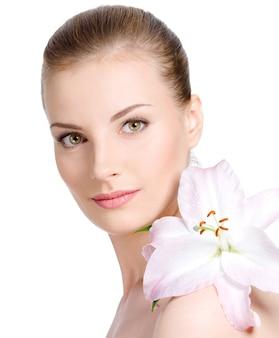 Ritratto del primo piano di bella giovane donna graziosa con il fiore con sguardo attraente