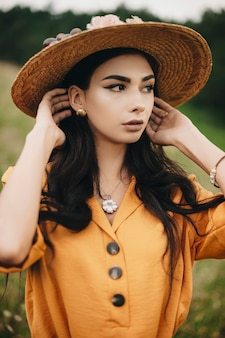 Close up portrait of a beautiful young woman looking away touching her hair outdoor. lovely female with dark hair wearing hat.