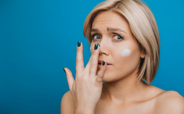 Close up portrait of a beautiful young woman looking at camera surfside while applying on her face and nice anti age white cream isolated on blue wall.