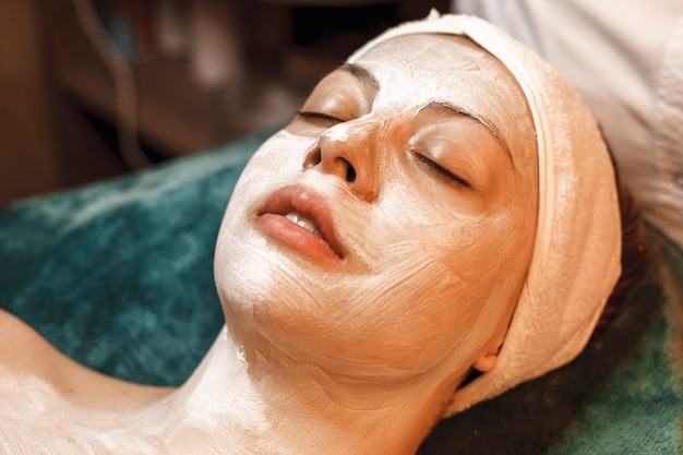 Close up portrait of a beautiful young woman resting while having a white skin care mask on her face in a wellness spa center.