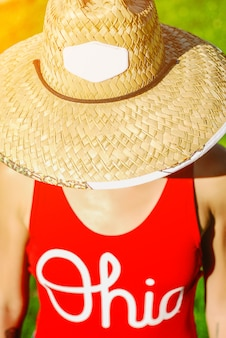 Close up portrait of a beautiful young woman in sexy red swimsuit and vogue vintage straw hat.