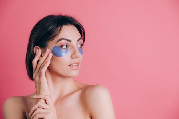 Ritratto del primo piano di una bella giovane donna in topless spalle aperte con cuscinetti di collagene blu sotto gli occhi. concetto di bellezza.