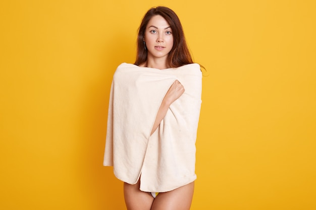 Close up portrait of beautiful young woman with dark staright hair posing wrapped fresh white bath towel