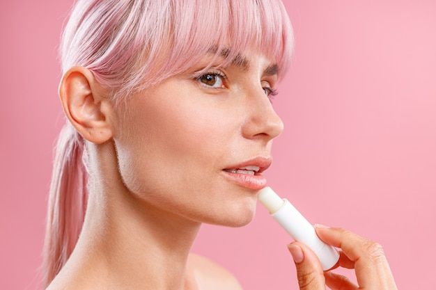 Close up portrait of beautiful young woman with pink hair looking aside applying lip balm on her