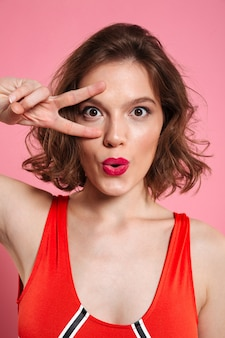 Close-up portrait of beautiful young woman with red lips showing peace gesture,