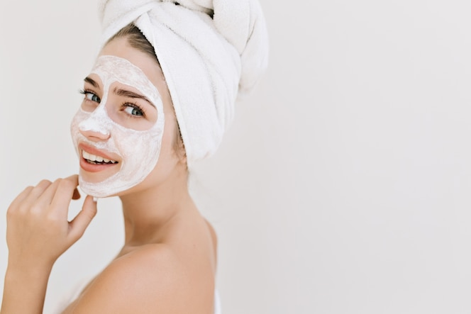 Close-up portrait of beautiful young woman with towels after take bath make cosmetic mask on her face.
