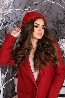 Chiuda sul ritratto della ragazza di bellezza nel parco di inverno gelido. bella giovane donna in cappello lavorato a maglia rosso, acconciatura incredibile ondulata, labbra carnose e trucco luminoso.