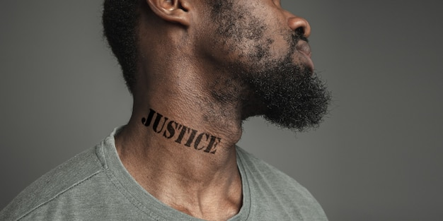Close up portrait black man tired of racial discrimination has tattooed slogan justice on his neck. concept of human rights, equality, justice, problem of violence and racism, discrimination. flyer.
