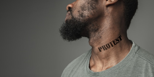 Close up portrait black man tired of racial discrimination has tattooed slogan protest on his neck. concept of human rights, equality, justice, problem of violence and racism, discrimination. flyer.
