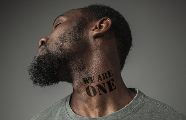 Close up portrait of a black man tired of racial discrimination has tattooed slogan we are one on his neck. concept of human rights, equality, justice, problem of violence and racism, discrimination.