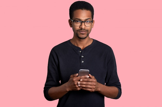Close up portrait of black man with short curly hair, little beard, holds smart phone in hands, writes massage to friends, dressed in casual outfit, isolated on white wall.