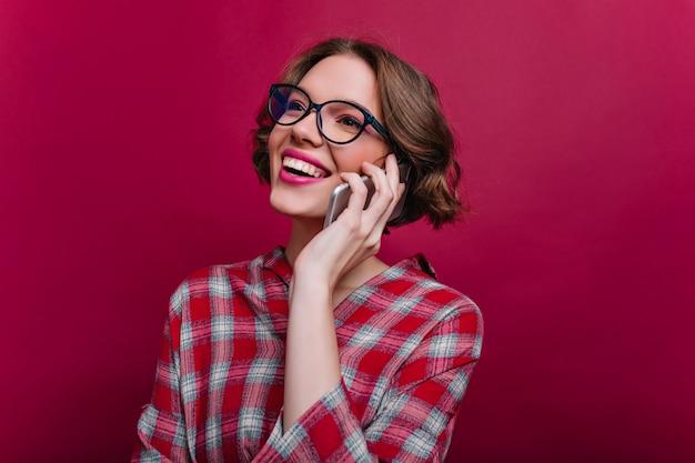 Ritratto del primo piano della ragazza castana beata con l'acconciatura riccia che parla sul telefono. attraente signora caucasica in bicchieri e camicia a scacchi in posa con lo smartphone sulla parete bordeaux.
