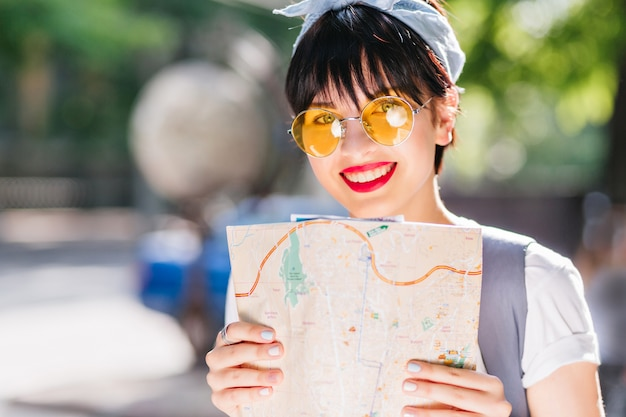Close-up portrait of blissful girl with shiny black hair enjoying new trip around world and smiling