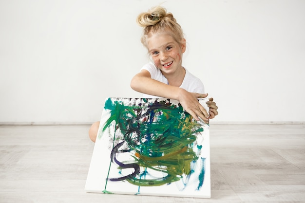 Close-up portrait of blond european little girl with hair bun and freckles smiling with all her teeth. holding on her knees picture that she painted for her parents, feeling proud of herself. people a