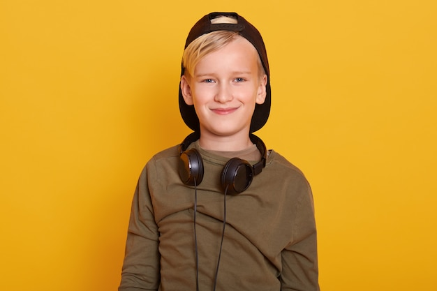 Close up portrait of blond little boy wearing casual clothes, cap, keeps headphones around neck