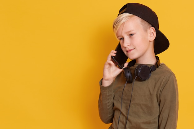 Close up portrait of blonde boy speaking by mobile phone and having pleasant facial expression, charming model posing isolated on yellow. copy space for advertisment or promotion.