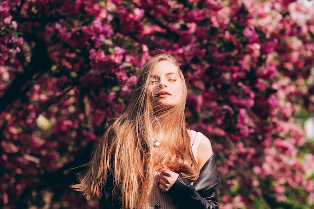 A close-up portrait of a blonde girl against the backdrop of a japanese flowering tree of sakura. a beautiful young woman with long blond hair in the spring park.