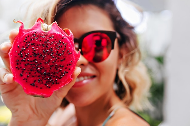 Close-up portrait of blonde girl in bright glasses posing with pitaya. winsome caucasian lady holding exotic fruit.