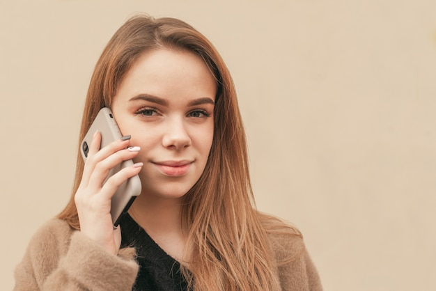 Close-up portrait of a blonde girl calls the phone and looks into the camera on the background of a beige wall, looking into the camera