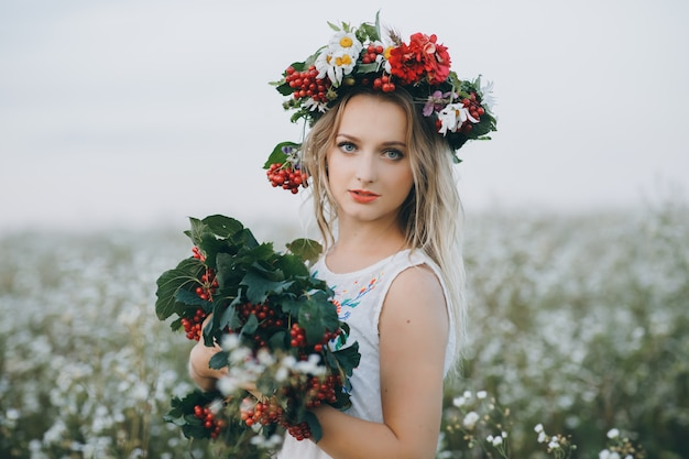 Close up portrait of a blonde girl with blue eyes with a wreath of flowers on her head