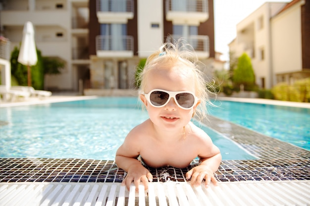 The close up portrait of a blonde smiling toddler girl, getting out of swimming pool.