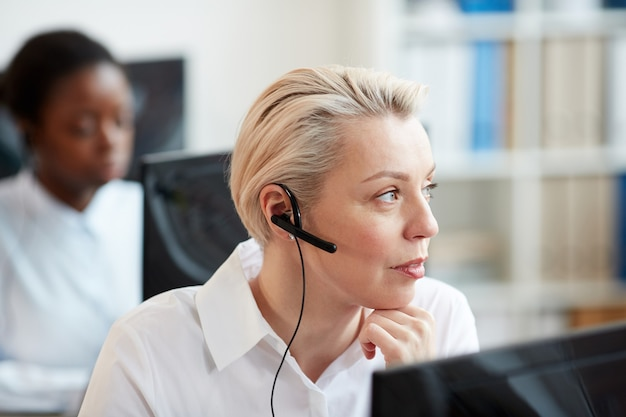 Close up portrait of blonde woman wearing headset and talking to customer while working in support service call center