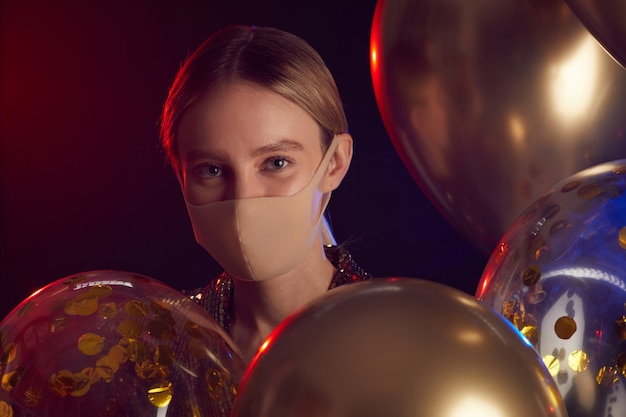 Close up portrait of blonde young woman wearing face mask and holding balloons while enjoying party in night club, copy space