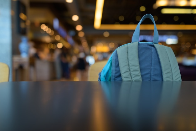 Close up portrait of blue backpack inside the mall against view of luminous lights