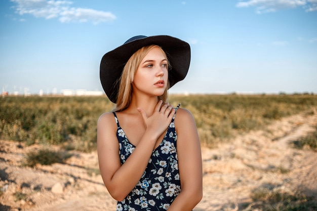 A close-up portrait of a blue-eyed blonde woman in a black hat and a floral print dress.she's posing in a vineyard during sunset