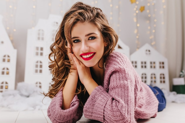 Close-up portrait of blue-eyed curly girl with red lipstick, smiling while lying on floor in cozy winter atmosphere with toy houses.
