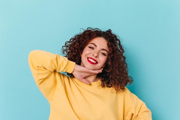 Ritratto del primo piano della ragazza dagli occhi azzurri con le labbra rosse. la donna riccia in maglione giallo tocca il suo mento e posa sullo spazio blu.