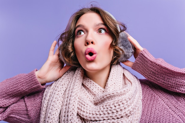 Close-up portrait of brown-eyed short-haired girl touching fur headphones. surprised european lady in woolen scarf isolated on purple wall.