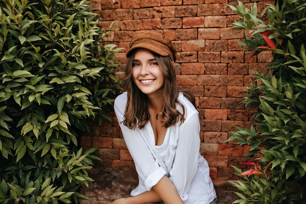 Close-up portrait of brown-eyed short-haired girl with gentle tattoo on her arm. woman in cap and v-neck blouse smiling on brick space with trees.