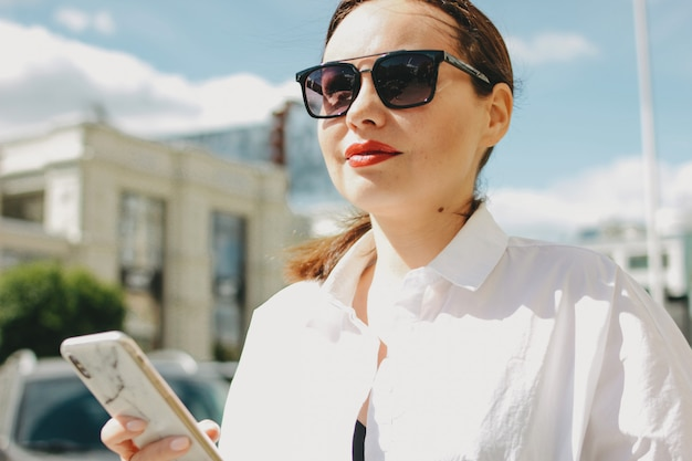 Close up portrait of brunette elegant woman business lady in sunglasses using mobile