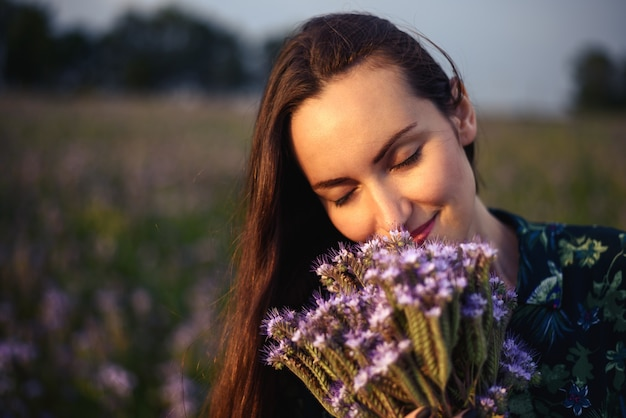 Close-up portrait of brunette in a floral meadow holds to be fresh wild flowers listening to the aroma