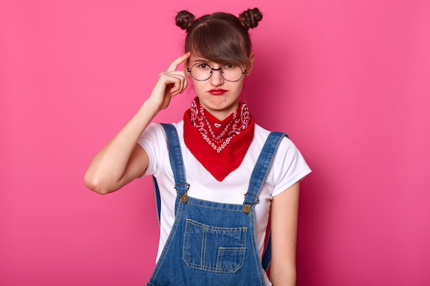 Close up portrait of brunette student, wears round eyewear and red bandana on neck, curves lips, keeps fore finger on temple
