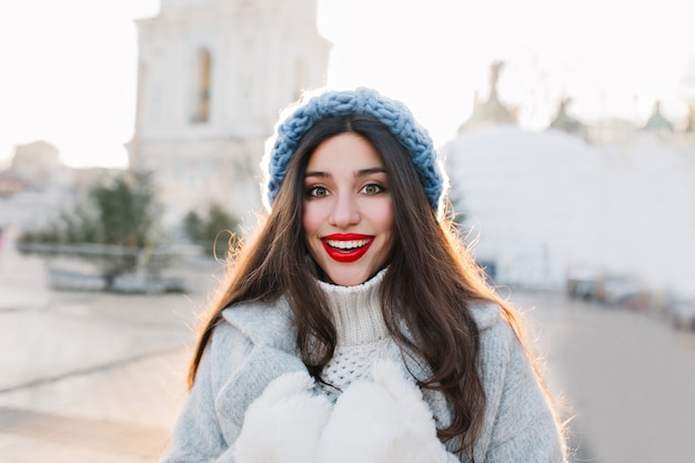 Close-up portrait of brunette woman with red lips smiling on blur city. outdoor photo of carefree girl in blue knitted hat and warm gloves posing with surprised face expression.