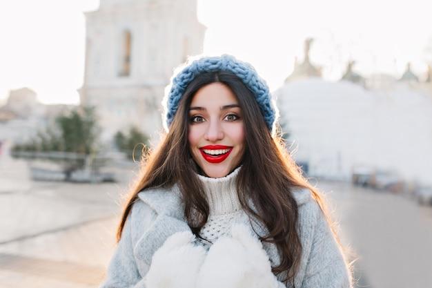 Ritratto del primo piano della donna castana con le labbra rosse che sorridono sulla città della sfuocatura. foto all'aperto di ragazza spensierata in cappello lavorato a maglia blu e guanti caldi in posa con l'espressione del viso sorpreso.