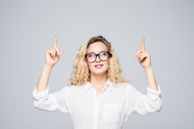 Close up portrait of business woman, pointing two forefingers up on empty place, looking at copy space, isolated on grey wall