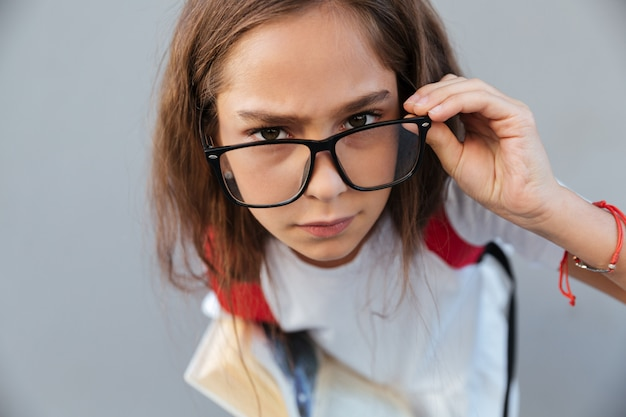 Close up portrait of calm brunette schoolgirl in eyeglasses
