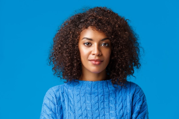 Close-up portrait calm and carefree good-looking african american female in sweater, with afro curly hairstyle, smiling cute and looking camera with friendly pleasant expression, blue