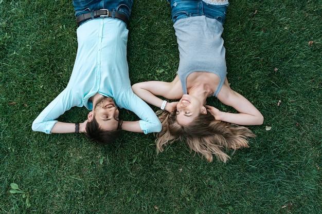Chiuda sul ritratto di coppia spensierata sdraiato sull'erba insieme nell'amore
