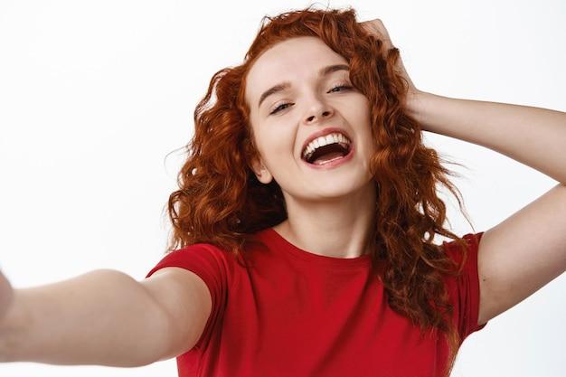 Ritratto ravvicinato di una ragazza zenzero spensierata e felice, che si tocca i capelli ricci naturali e ride mentre si fa selfie sul muro bianco