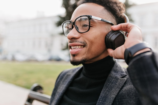 Close-up portrait of carefree mulatto boy isolated. outdoor photo of chilling brunette male model with brown skin posing in headphones.
