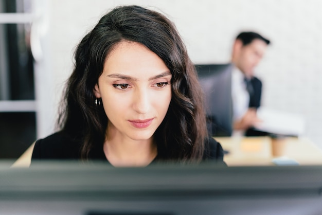 Close-up portrait of a caucasian businesswoman typing and looking on a computer screen with intention at her desk.