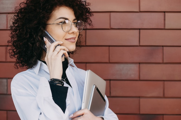 Close up portrait of caucasian curly woman talking on phone while posing on a stone wall with some gadgets