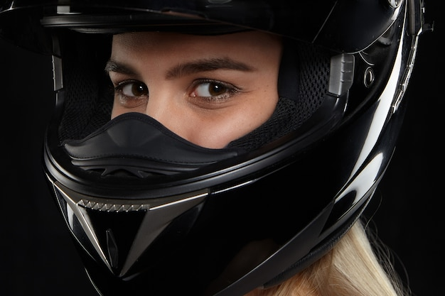 Close up portrait of caucasian female motorcycle racer with happy eyes wearing black modern safety helmet, going to competition, feeling excited. speed, extreme, danger and activity concept