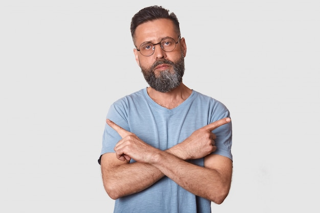 Close up portrait of caucasian male points at different sides with index fingers, cant choose between two items, has calm expression, wearing glasses and gray t shirt, isolated over white wall.