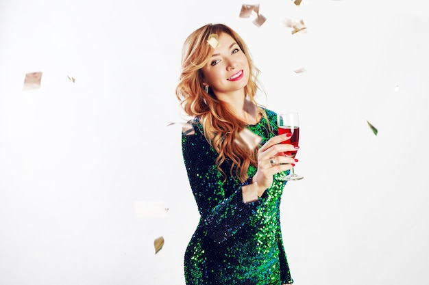 Close up portrait of  celebration woman in green sequin  dress drinking wine, enjoying party. golden confetti.
