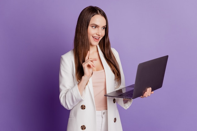 Close up portrait of charming business lady hold computer look screen work on purple wall